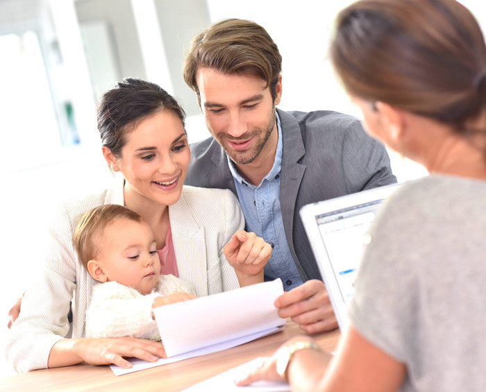a couple with a baby looking at paperwork